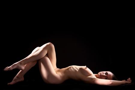 Beautiful young woman  posing nude on black