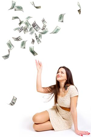 seating: Young woman throwing 100 dollar bills up isolated on white