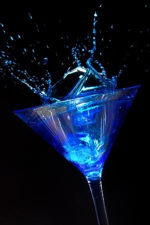 martini splash: Blue Martini Cocktail with splash on black
