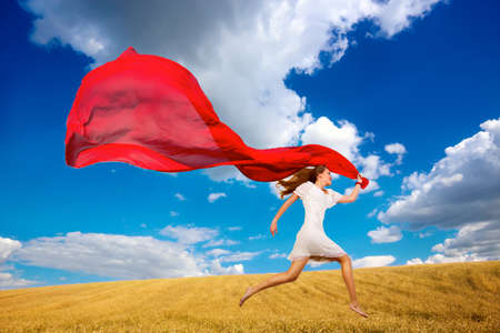 Young beautiful woman running in wheat field with red fabric photo