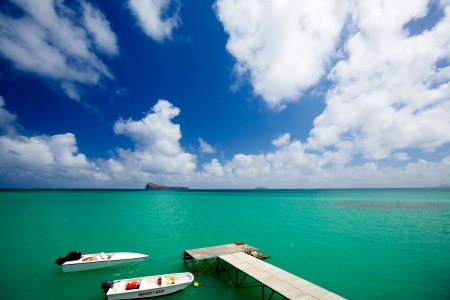 mauritius: Calm scene with jetty, boats and turquoise water in Mauritius Stock Photo