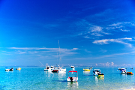 Catamaran and boats in turquoise sea of Mauritius early morning