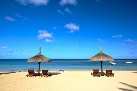 Tropical beach with lounge chairs and umbrella in Mauritius