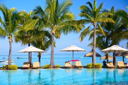 resort beach: Swimming pool with  lounge chairs and umbrellas on beach in Mauritius