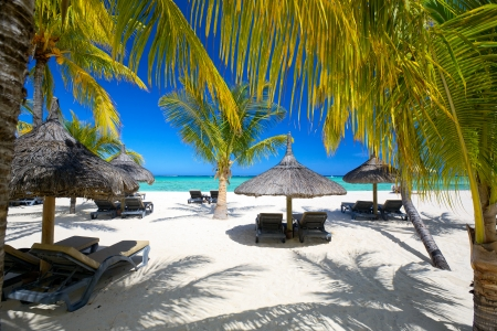 Lounge chairs with umbrellas on white sand beach, Mauritius Banque d'images