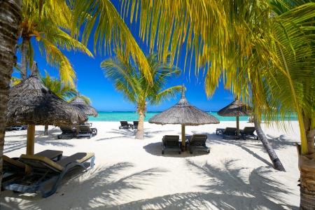 Lounge stoelen met parasols op wit zandstrand, Mauritius