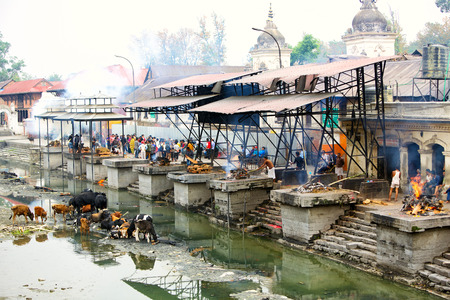 cremation: Kathmandu, Nepal - May 04, 2014: Cremation ghats and ceremony along Bagmati River at Pashupatinath Temple