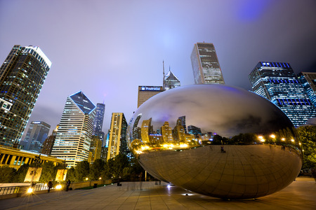 Chicago, Illinois, USA - September 15, 2014: Chicago Cloud Gate sculpture and downtown Chicago skyline buildings in Millenium Park at night 에디토리얼