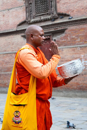 limosna: Katmandú, Nepal - 03 de mayo 2014: Monje budista con el tazón de pie a pedir limosna a la Plaza Durbar de Katmandú, Nepal.