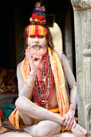 sadhu: Kathmandu, Nepal - May 04, 2014: Holy Sadhu man with beard and traditional face paint sitting in Pashupatinath Temple.