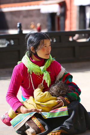 begs: Shigatse, Tibet, China - May 10, 2014: Unidentified local woman with child begs alms at Tashilhunpo Monastery area. Editorial