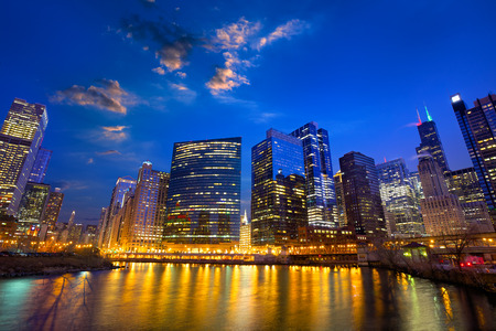 Chicago River and skyscrapers in financial district at dusk, IL, US
