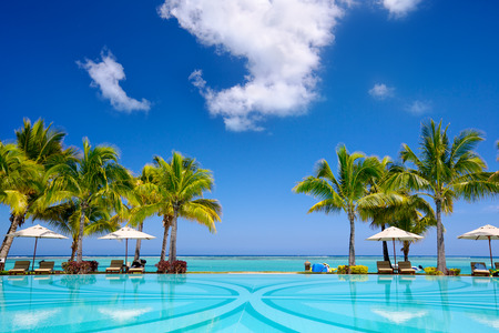 exotic fruits: Tropical beach resort with  lounge chairs and umbrellas in Mauritius Stock Photo