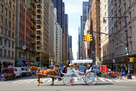taxi famous building: New York, New York, USA - May 11, 2016: Avenue of the Americas (Sixth avenue) traffic with Central Park Horse Carriage crossing intersection