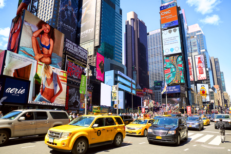 New York, New York, USA - May 08, 2016: Cars and taxi cabs on 7th Avenue and Broadway in Times Square with crowds of people and lots of advertising