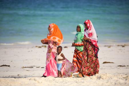 mujeres africanas: Kiwengwa Beach, Zanzibar, Tanzania - January 09, 2017: Local women with child walking along beach in traditional colorful clothes