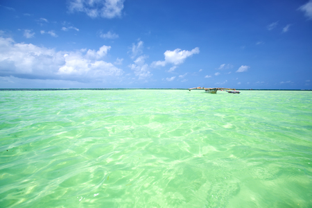 turquoise water: Tropical lagoon with turquoise water and boat in Zanzibar Stock Photo