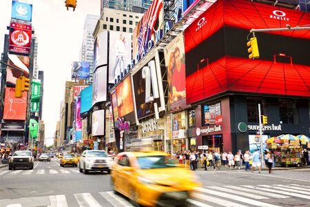 NEW YORK CITY, NY, USA - SEPTEMBER 15, 2018: Yellow taxi crossing intersection at Times Square with lots of animated LED billboard advertising