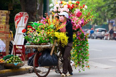 HOI AN, VIETNAM - JANUARY 3, 2010: Typical vietnamese vendor sells flowers on her bicycle at street in Hanoi
