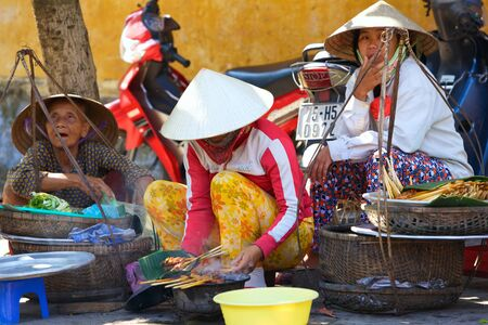HOI AN, VIETNAM - JANUARY 6, 2010: Typical street vendors sell fresh food in Hoi An
