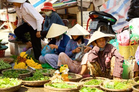 HOI AN, VIETNAM - JANUARY 6, 2010: Vietnamese street vendors sell fresh vegetables at local market in Hoi An Editöryel