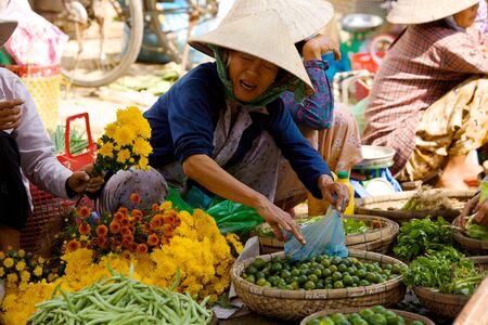 HOI AN, VIETNAM - JANUARY 6, 2010: Vietnamese street vendors selling vegetables at local market in Hoi An Editöryel