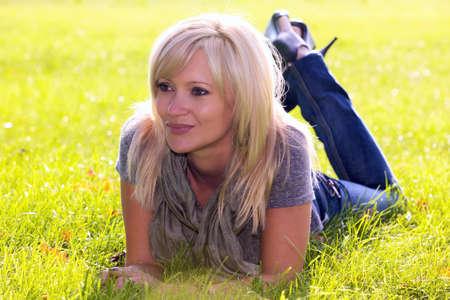 Pretty woman lying on bright green grass Stok Fotoğraf