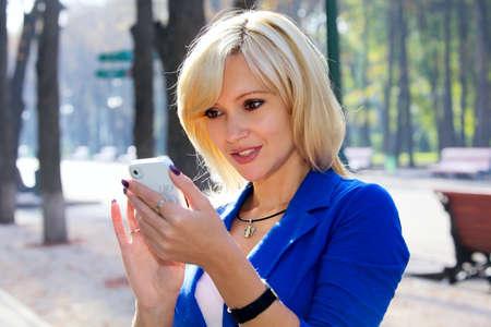 Beautiful blond woman text messaging on smart phone Stok Fotoğraf