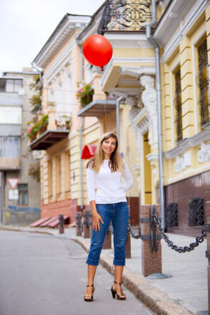 Smiling woman with red baloon standing on street Stok Fotoğraf