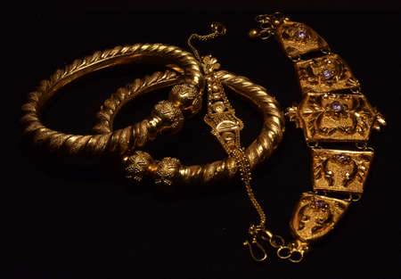 Indian traditional Gold Jewellery displayed on a dark background