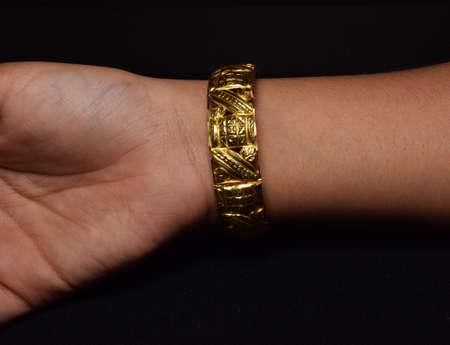 Closeup of girl wearing Indian traditional designer gold bracelets