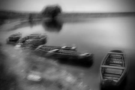 Blurry long exposure image of storm at Danube river with fishing boats