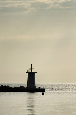 the silhouette of the lighthouse at the breakwater, minimalism