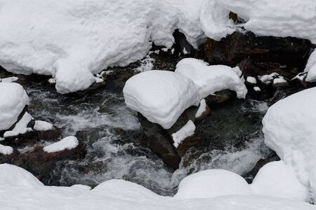 a beautiful mountain stream with romantic snowcapped rock in the form of a heart 스톡 콘텐츠