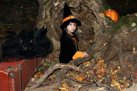 Witch child with a pumpkin on Halloween photo
