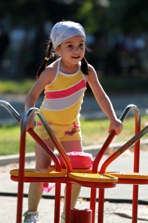 Happy and cute little girl on playground photo