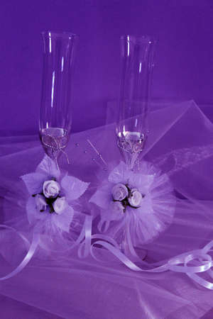 Beautiful wedding glasses with ribbon on violet background photo