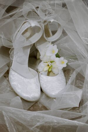 Wedding shoes and white freesia on veil background photo