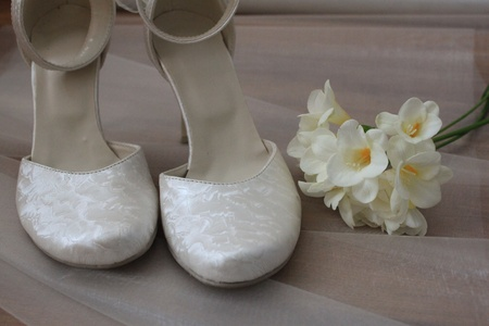 Bridal shoes and bouquet of freesia flowers photo