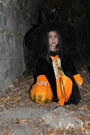 Witch child with a pumpkin in Halloween eve photo