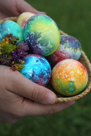 Toddlers hands holding easter eggs in basket