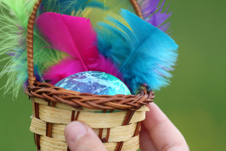 Toddlers hand holding easter egg in basket