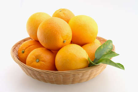 Fresh Oranges stacked in a basket and Isolated
