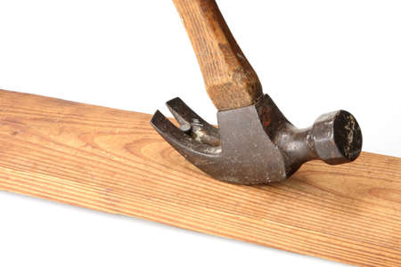 pry: Old hammer pulling nail from piece of wood