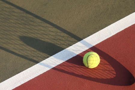 Tennis ball by line shadow of tennis racket