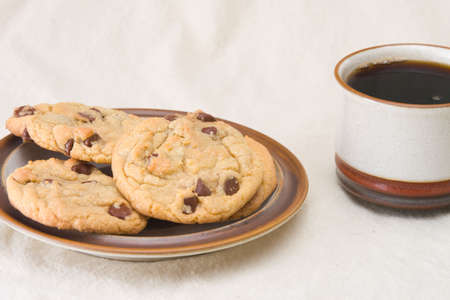 Plate of chocolate chip cookies and cup of coffee Stock Photo