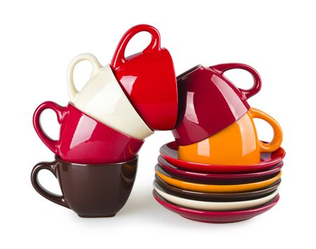 saucers: Stack of colorful mugs and saucers on white background