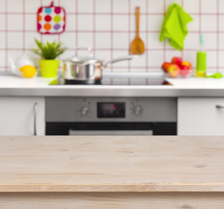 red kitchen: Wooden table on blurred kitchen bench background