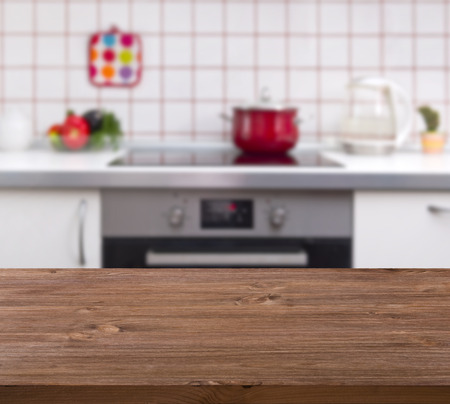 red kitchen: Wooden table on kitchen bench background