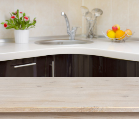 Wooden table on kitchen faucet interior background